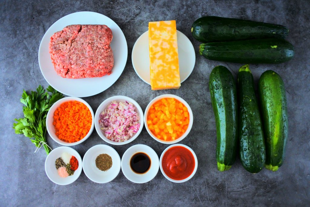 An overhead image of ingredients for zucchini boats including ground beef, cheese, zucchini, fresh parsley, carrots, onion and garlic, butternut squash, spices, Worcestershire sauce and tomato sauce
