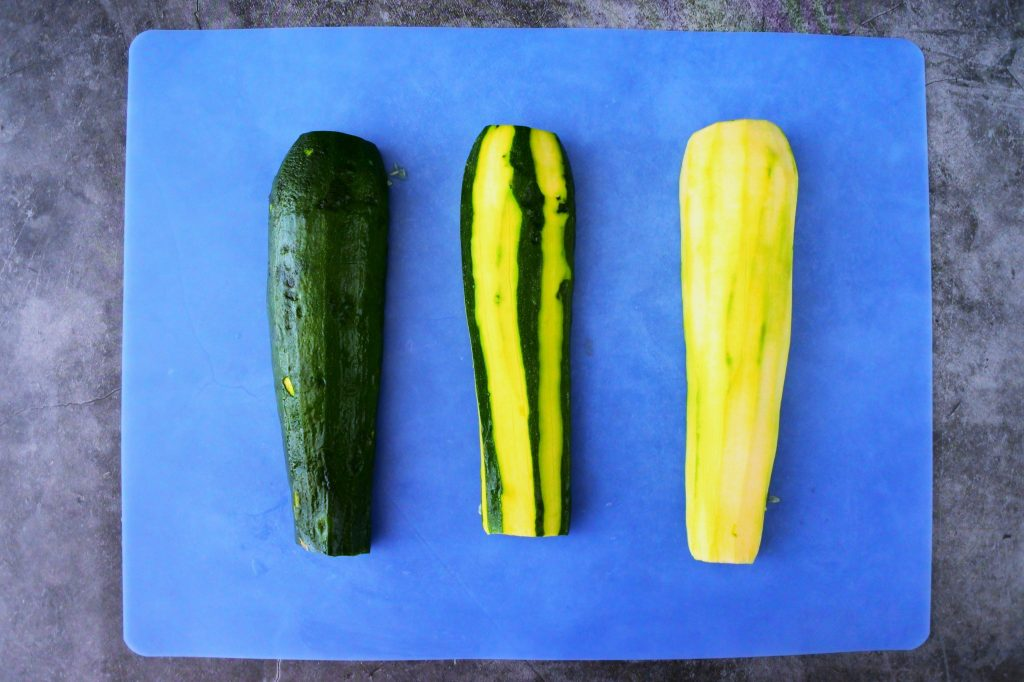 An overhead image of three zucchini halves, one with skin on, one with strips of skin removed and one peeled on a blue cutting mat