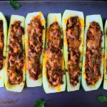 An overhead image of baked zucchini boats next to each other on a tray with leaves of fresh parsley around it