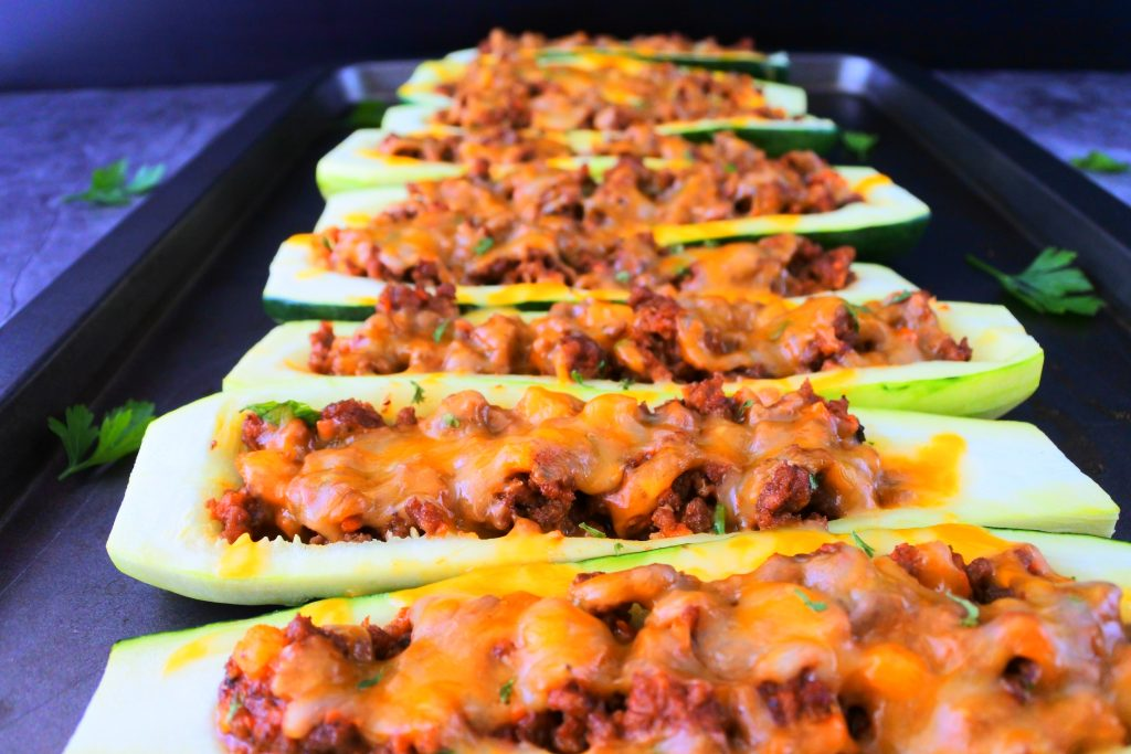 A head on angled image of baked zucchini boats next to each other on a tray with leaves of fresh parsley around it