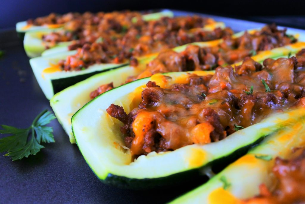 An angled image of baked zucchini boats next to each other on a tray with leaves of fresh parsley around it