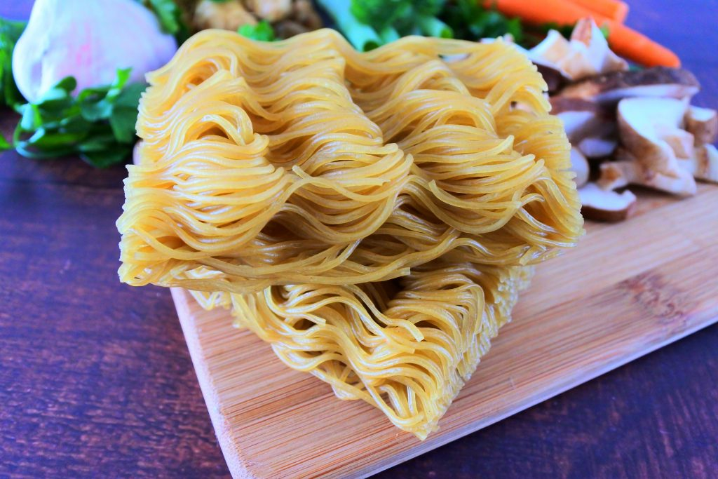 A close up image of two bricks of dry uncooked brown rice ramen noodles on a wood board with fresh vegetables in the background