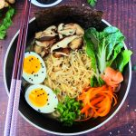 An overhead image of a plated bowl of chicken shoyu ramen topped with egg, mushrooms, bok choy, carrots, chicken, pickled ginger, chives and noodles. Surrounded by chopsticks, fresh herbs and a dish of black sesame seeds