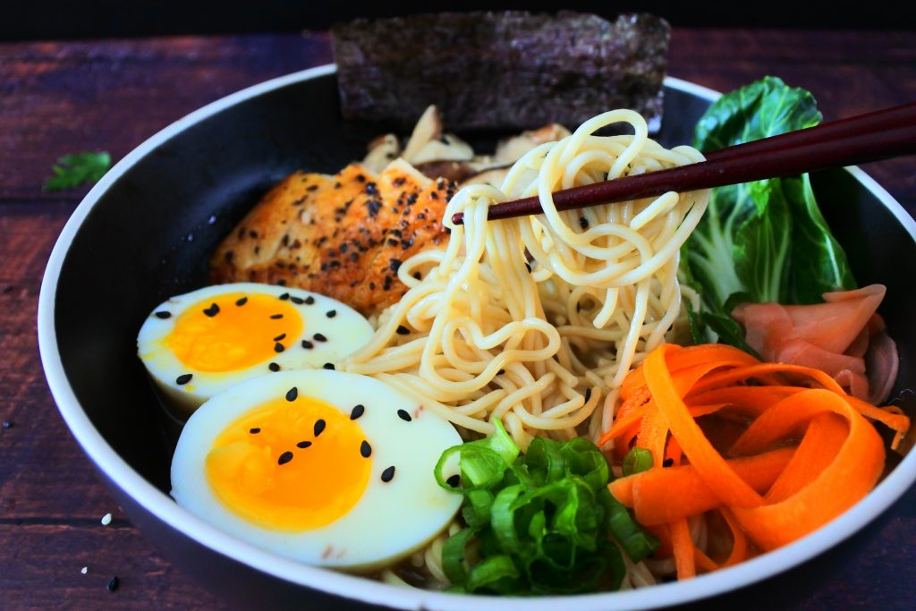 A close up image of some ramen noodles being lifted out of a homemade chicken shoyu ramen bowl
