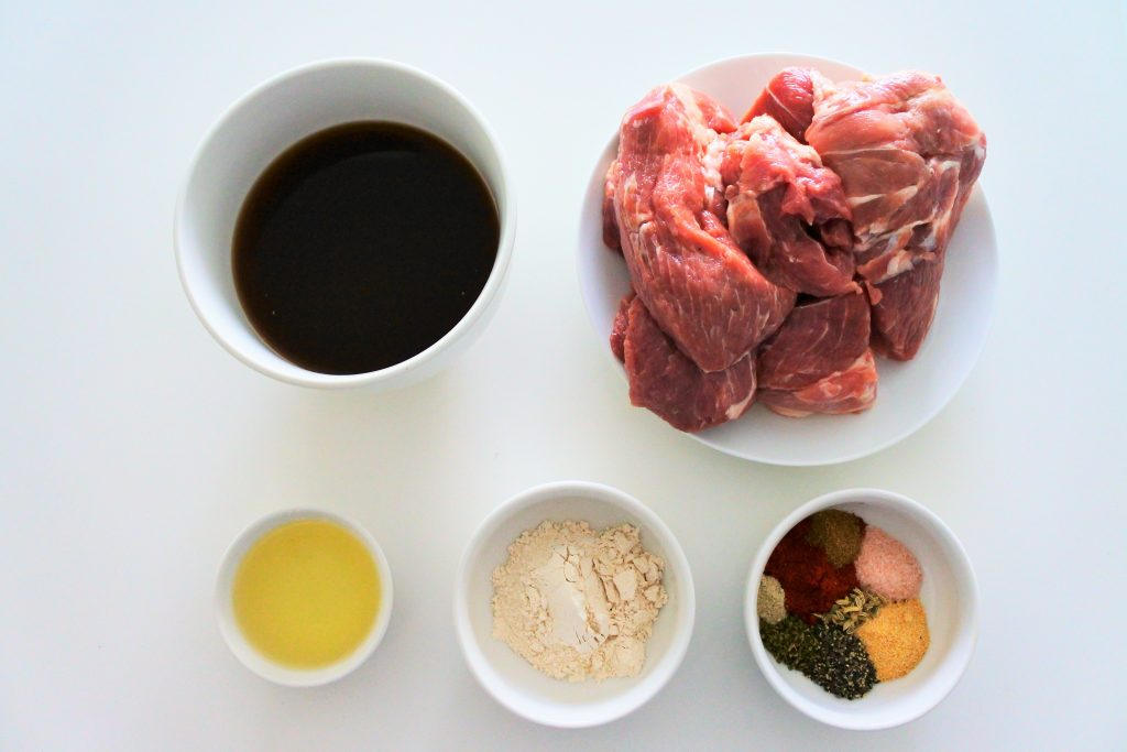 An overhead image of ingredients for oven roasted pork including beef broth, large pork chunks, oil, and herbs and spices for a rub
