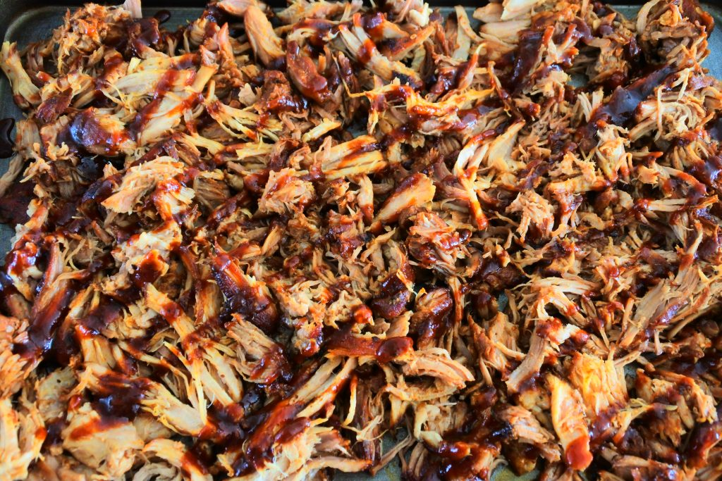 A close up image of pulled pork shredded with homemade bbq sauce drizzled over it.