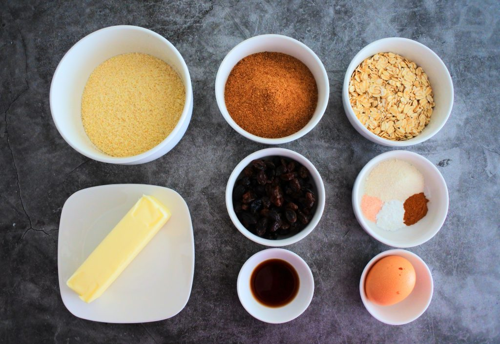 An overhead image of bowls of ingredients for oatmeal raisin cookies including almond flour, butter, coconut sugar, raisins, vanilla extract, oats, coconut flour, salt, baking powder, cinnamon and an egg