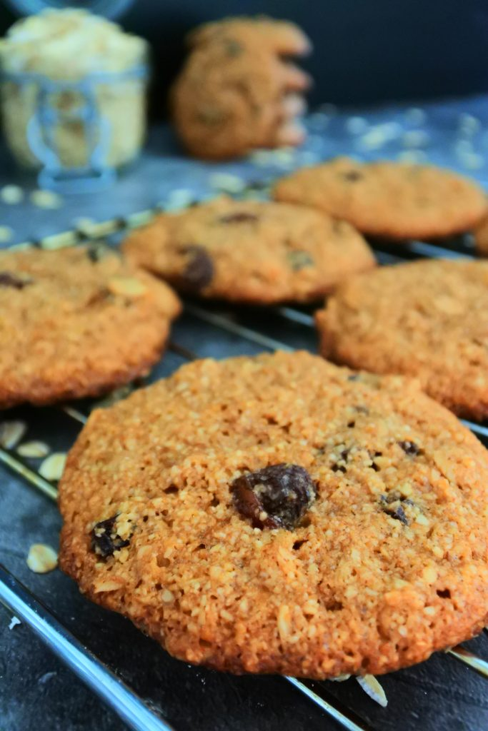 A close up image of oatmeal raisin cookies on a cooking rack