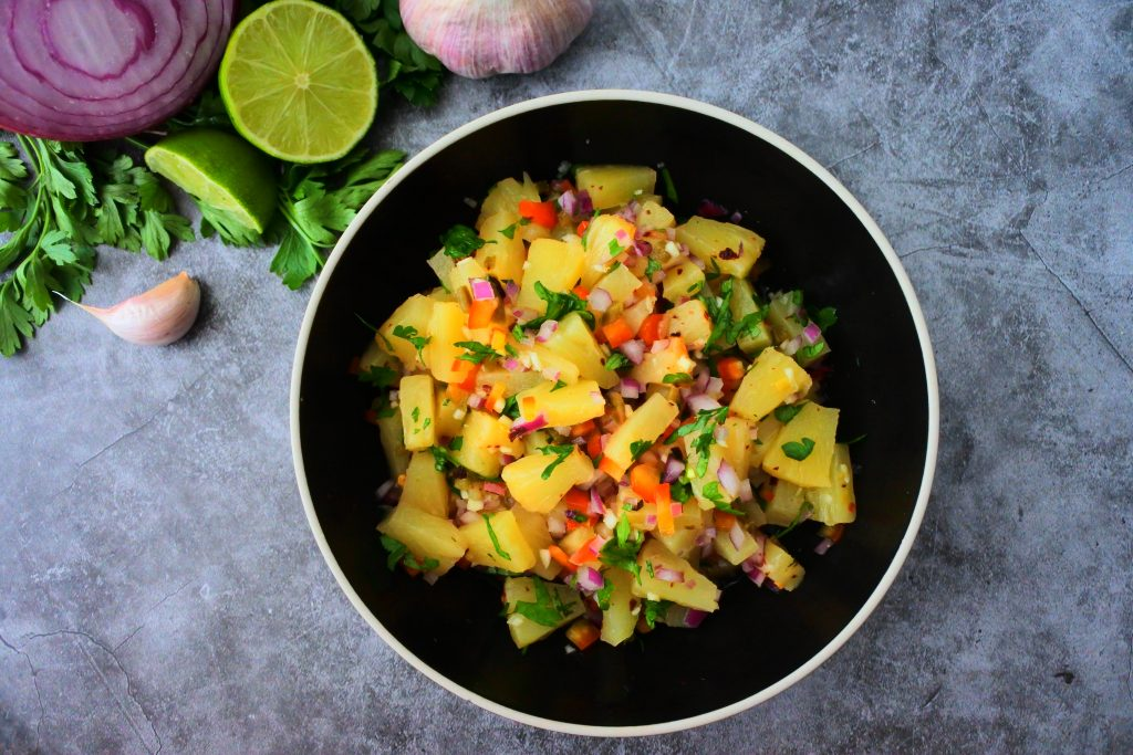 An overhead image of a bowl of pineapple salsa with fresh herbs in the top left corner