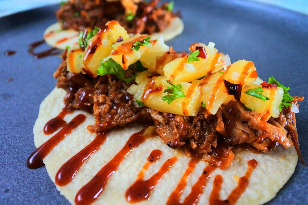A head on image of a BBQ pulled pork taco topped with pineapple salsa