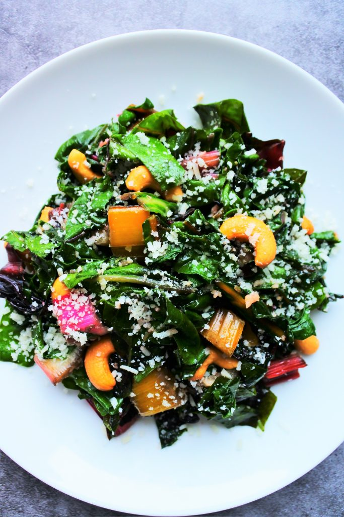 An overhead image of sauteed rainbow chard on a plate dressed with cashews and shredded cheese with a head of garlic, a wedge of cheese and greens and a skillet with sauteed chard in the background
