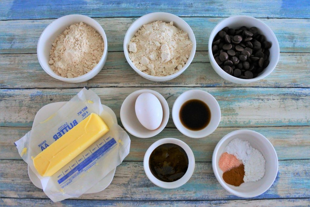 An overhead image of ingredients for a classic whole wheat cookie including whole wheat pastry flour, raw cane sugar, dark chocolate chips, butter, egg, vanilla extract, molasses, baking powder, baking soda, salt and cinnamon