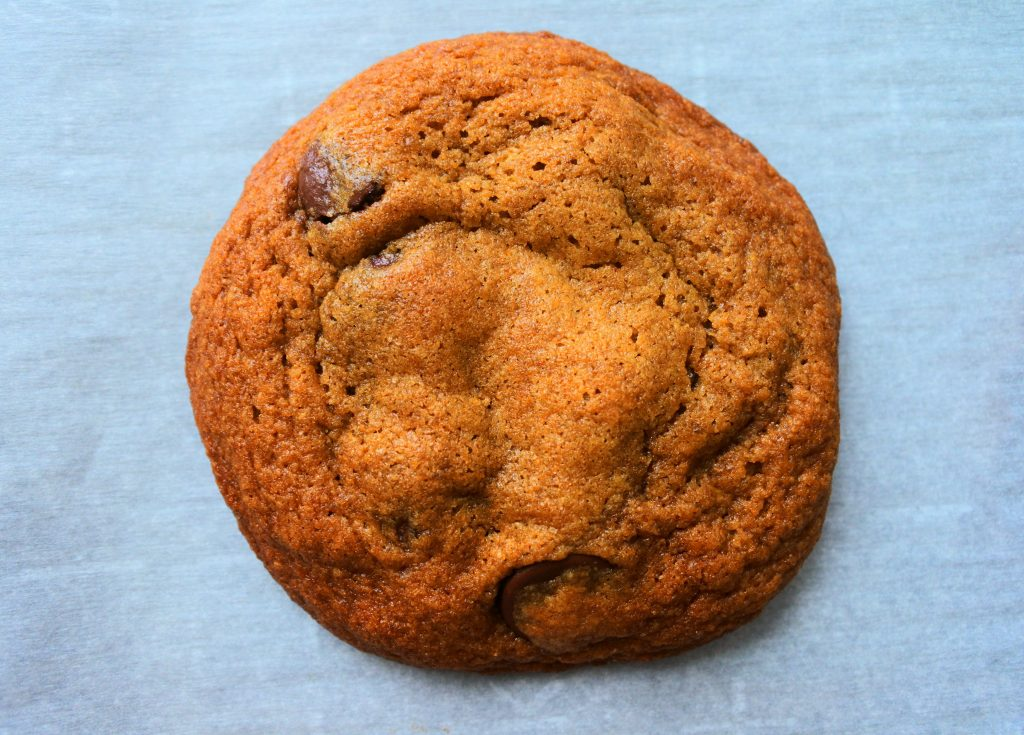 A close up overhead image of a baked classic chocolate chip cookie