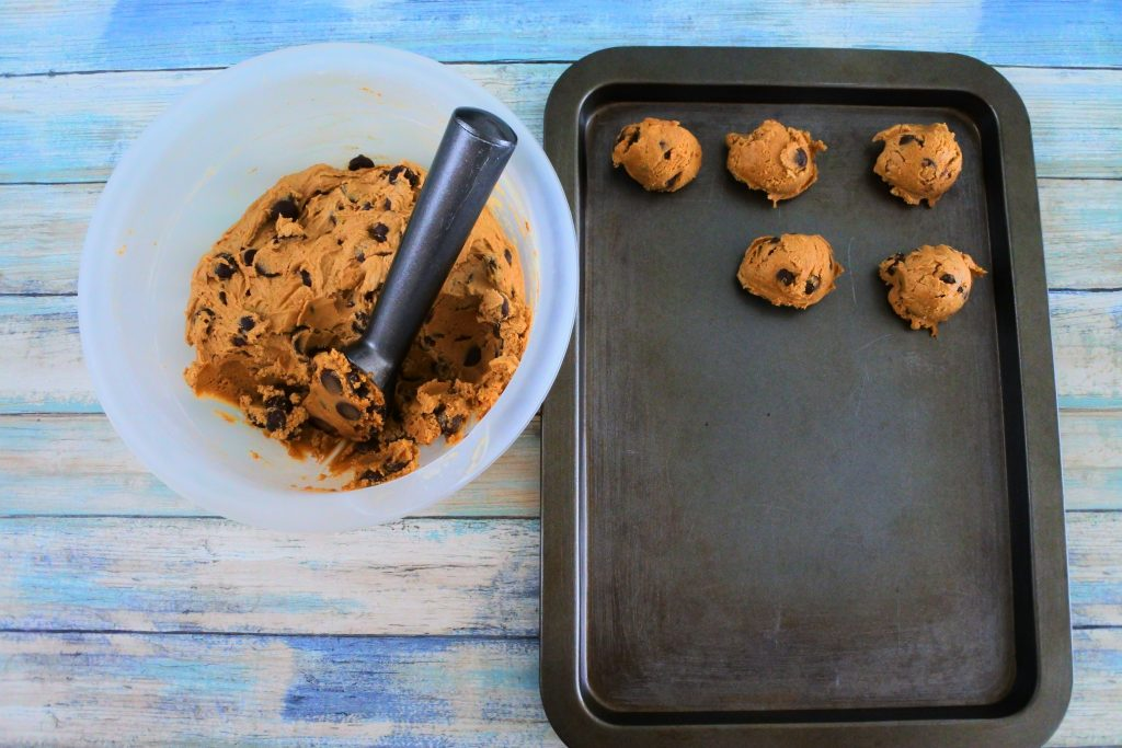 An angled overhead image of a bowl of chilled chocolate chip cookie dough with a scooper in it and a tray with portions of dough on the side