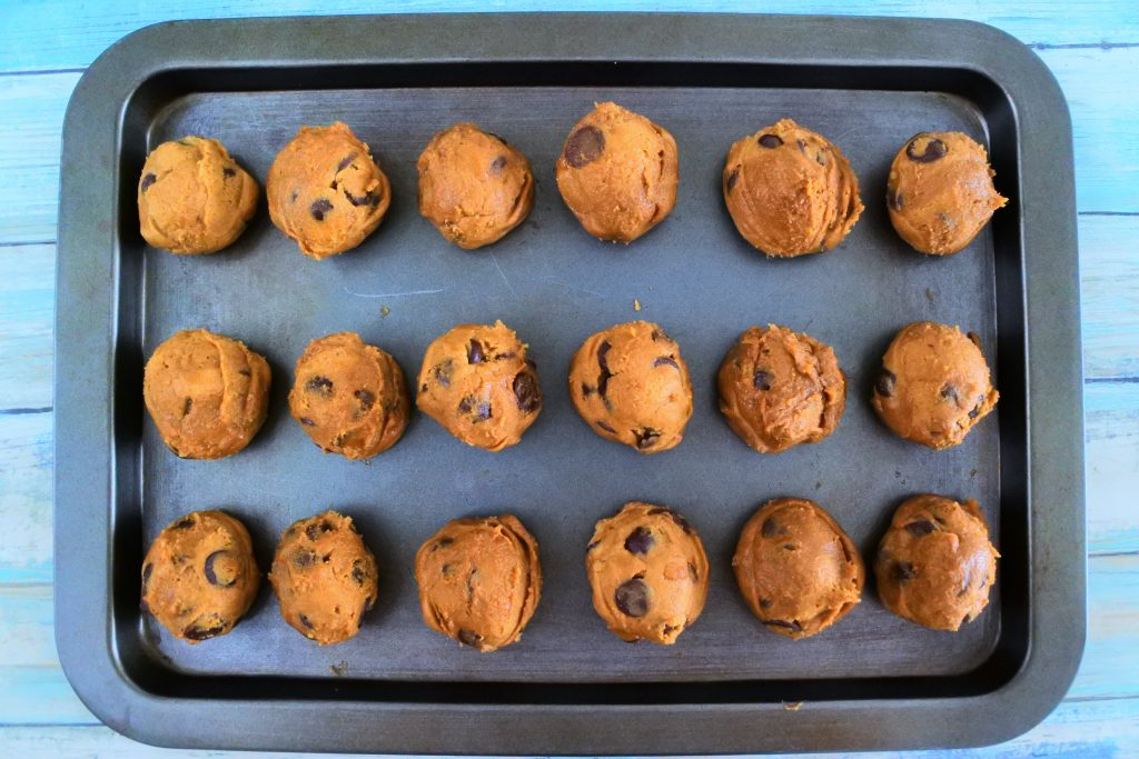 An overhead image of a tray of portioned out chocolate chip cookie dough