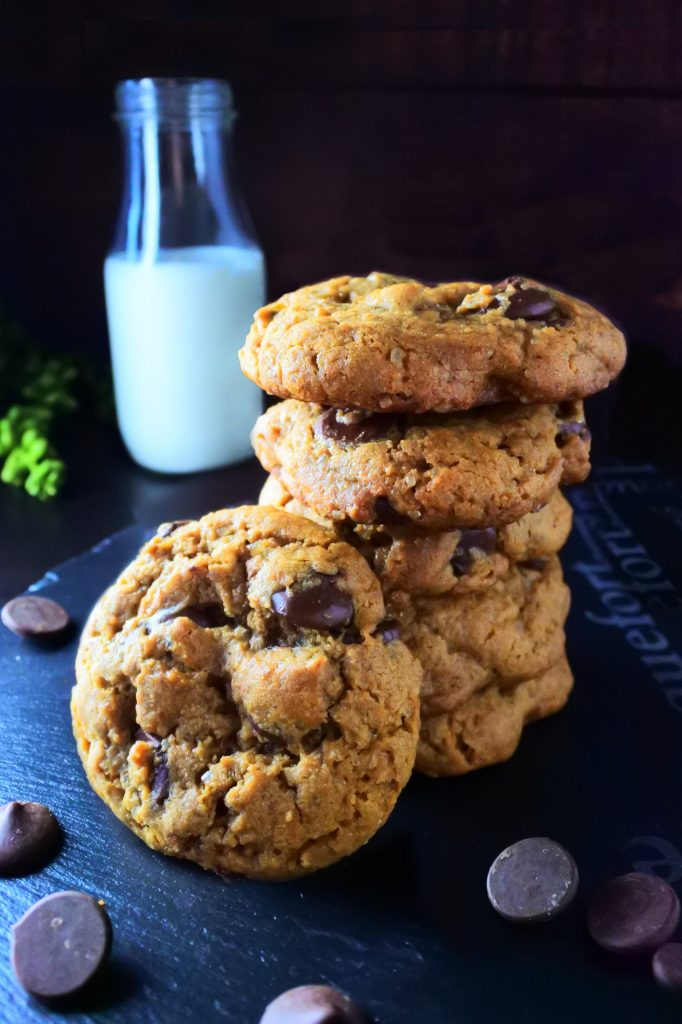 A stack of classic chocolate chip cookies with one cookie leaning against the side of the stack surrounded by chocolate chips with a bottle of milk in the background