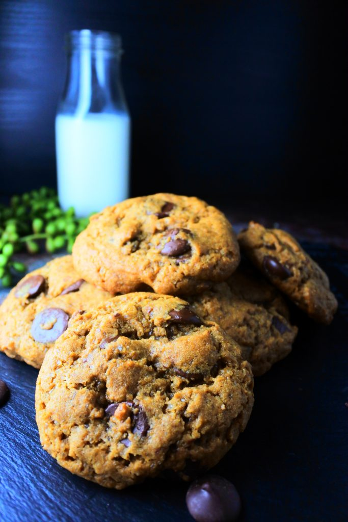 A pile of classic chocolate chip cookies with a bottle of milk in the background
