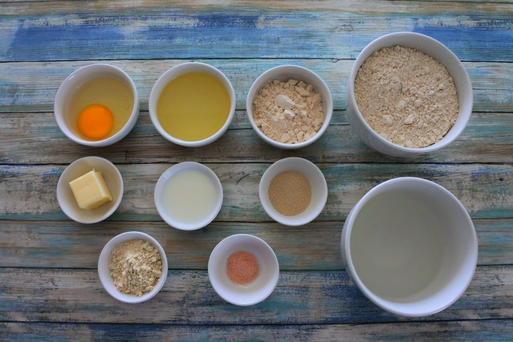 An overhead image of ingredients for one hour dinner rolls including whole wheat pastry flour, sugar, oil, egg, butter, milk, yeast, warm water, vital wheat gluten and salt