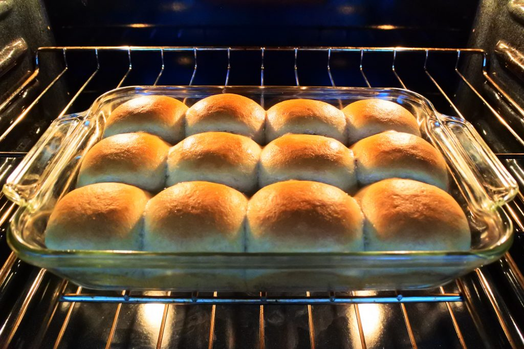 An angled image of freshly baked dinner rolls in a baking dish in the oven