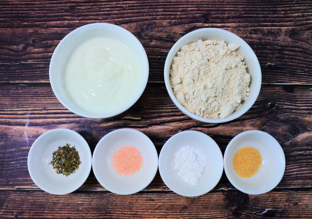 An overhead image of bowls of ingredients for making an easy whole wheat flatbread