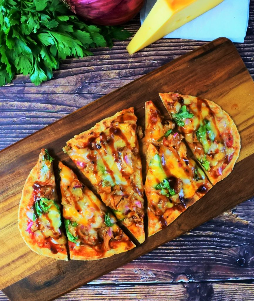 An overhead image of a BBQ chicken pizza flatbread on a board with fresh herbs and a block of cheese bordering the image