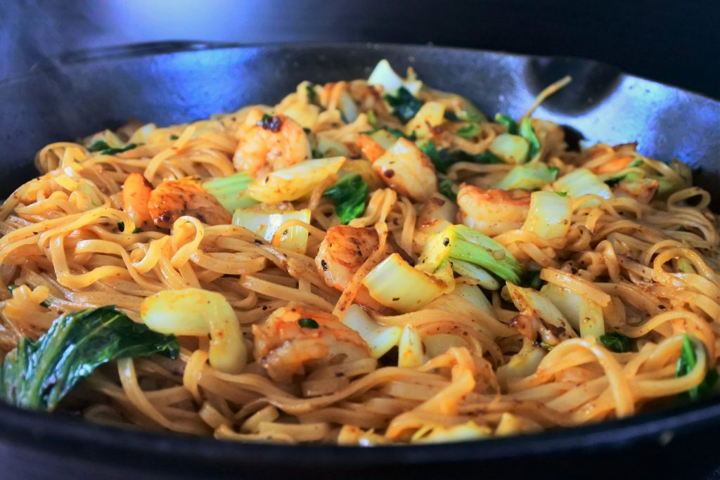 A close up image of shrimp noodle stir fry in a skillet