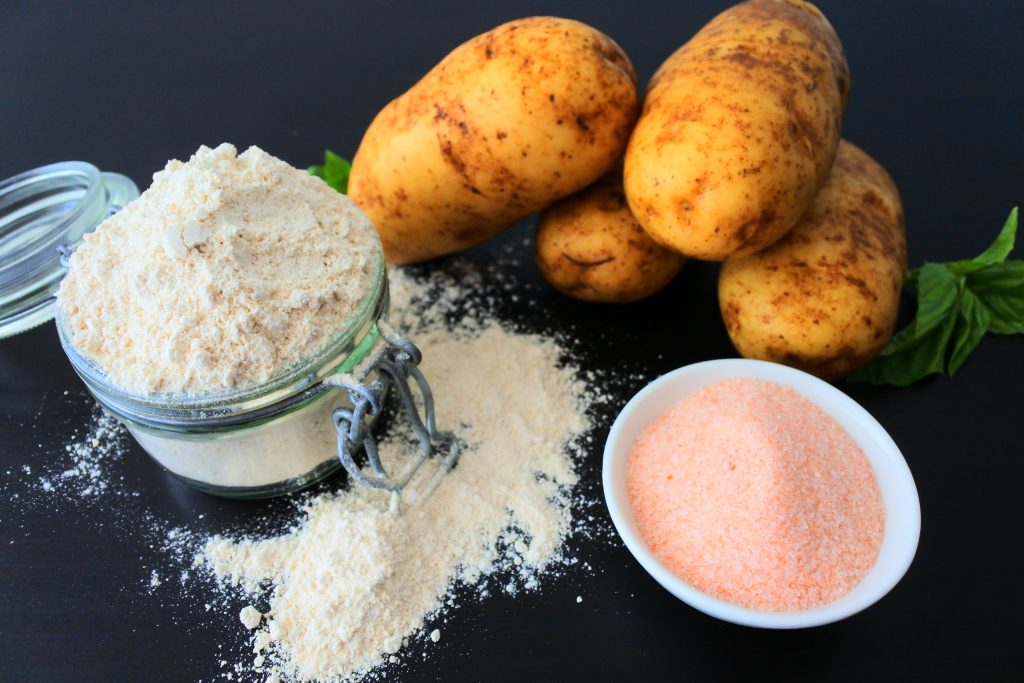 An angled image of ingredients for homemade potato gnocchi including whole wheat pastry flour, potatoes and salt