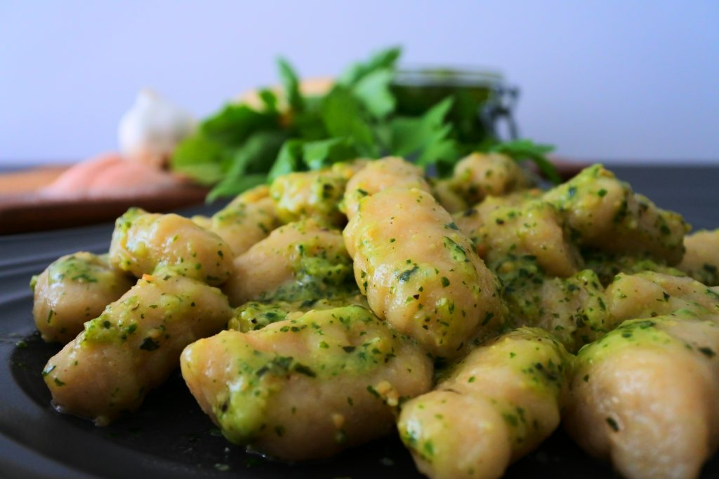 A head on image of a plate of pesto tossed potato gnocchi on a plate with ingredients on a wooden board in the background
