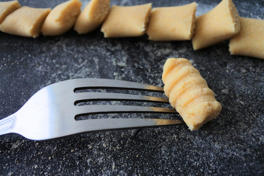 A close up image of potato gnocchi being shaped and rolled on the tines of a fork