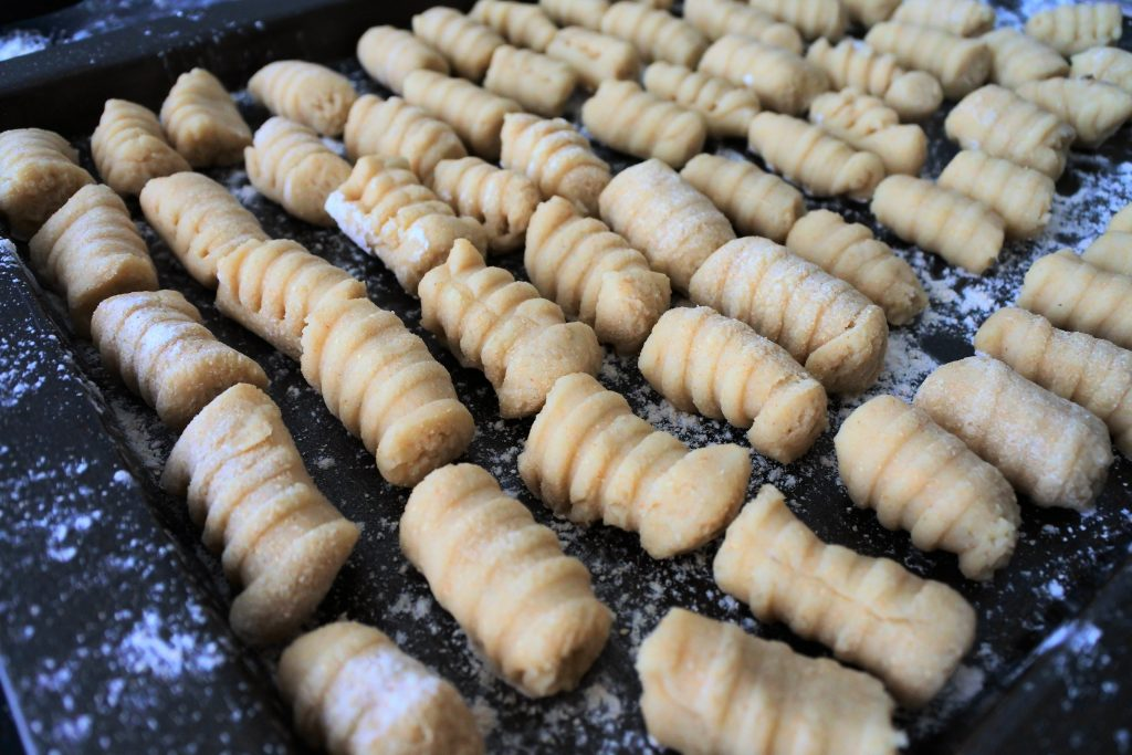An angled image of a floured tray of rolled and shaped potato gnocchi