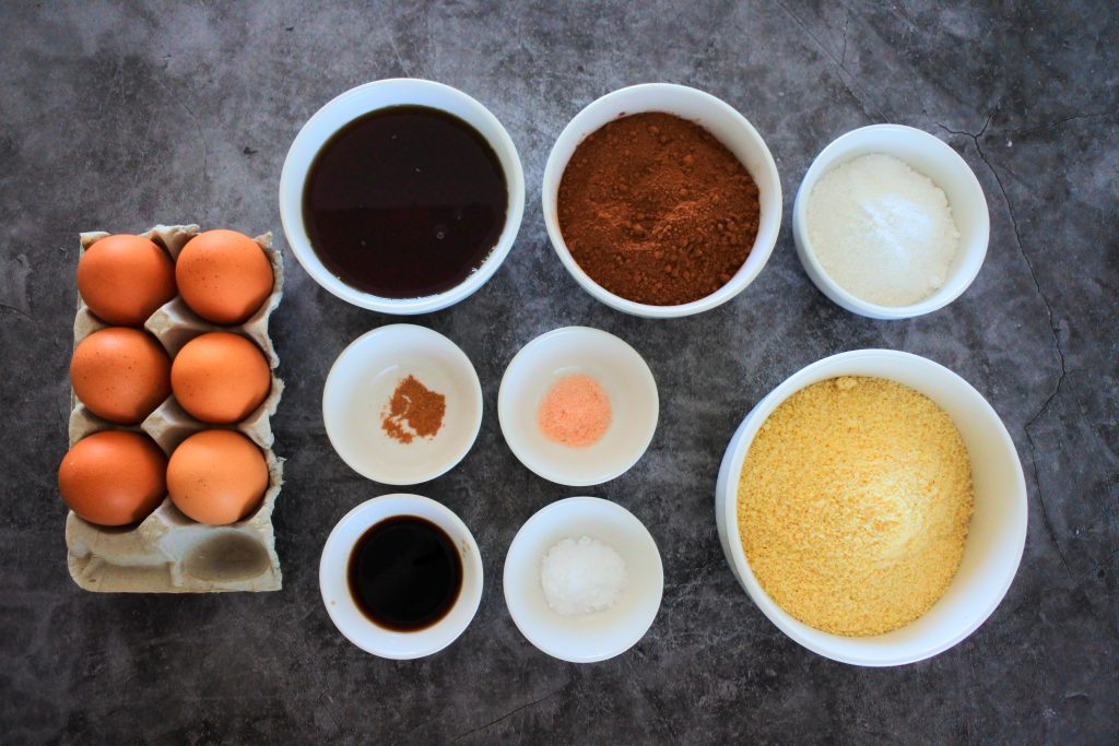 An overhead image of ingredients for almond flour chocolate cake including eggs, maple syrup, cocoa powder, finely blended sugar, almond flour, salt, nutmeg, vanilla extract and baking soda