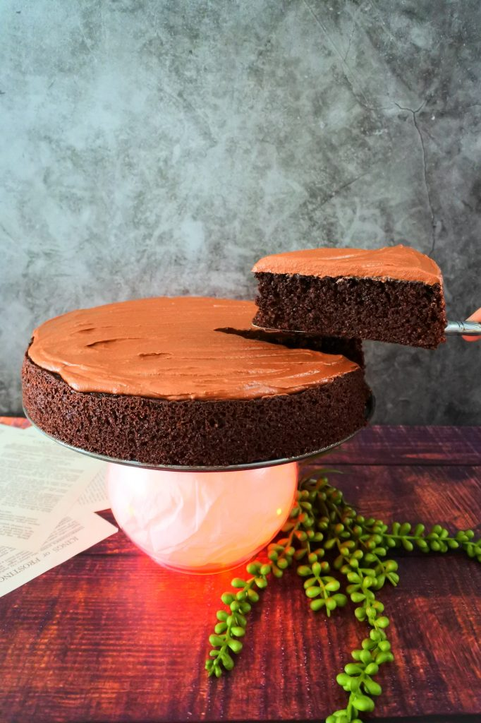 A head on image of a slice of chocolate frosted almond flour chocolate cake being cut and lifted to be served