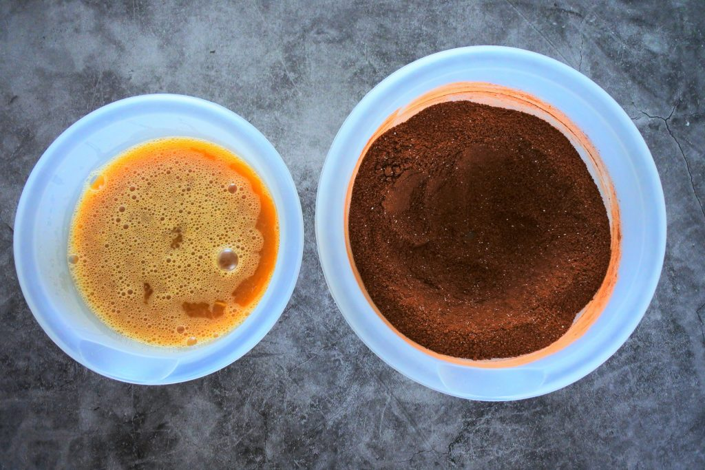 An overhead image of two bowls one containing wet ingredients and the other containing dry ingredients for an almond flour chocolate cake