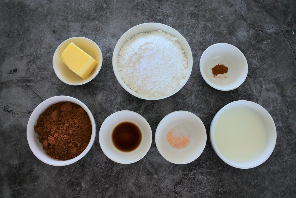 An overhead image of ingredients for homemade chocolate frosting including butter, finely blended cane sugar, cinnamon, cocoa powder, vanilla extract, salt and milk