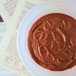 An overhead image of a bowl of chocolate frosting on scattered sheets of recipe pages