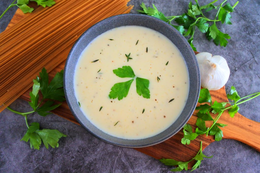 An angled image of a bowl of homemade Alfredo sauce in a stone bowl on a wooden plank surrounded by a small head of garlic, dried pasta and fresh parsley