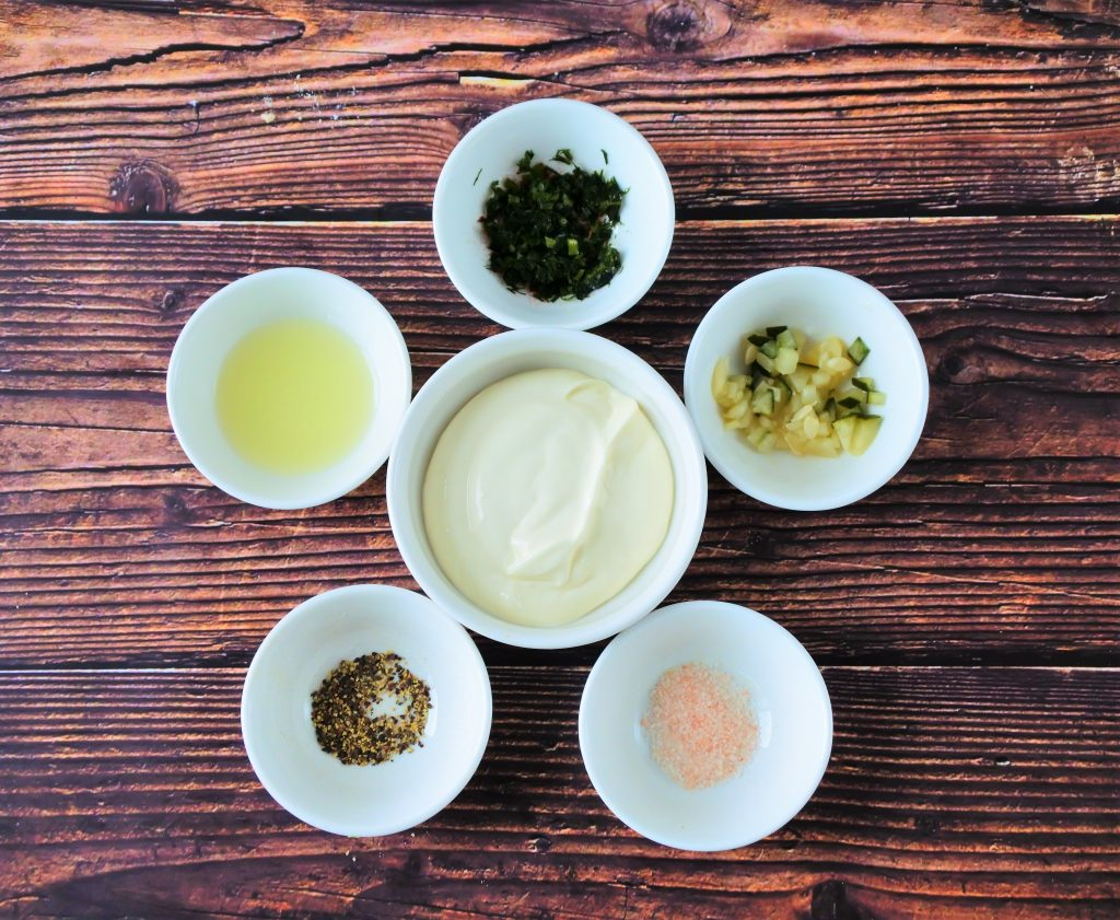 An overhead image of dishes of ingredients for a tartar sauce including Greek Yogurt, homemade pickles, salt, pepper, lemon juice and dill