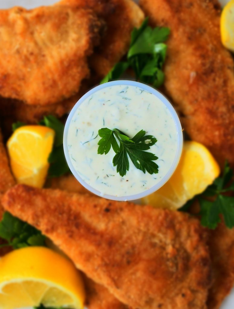 A close up image of a dish of tartar sauce surrounded by lightly fried fish fillets