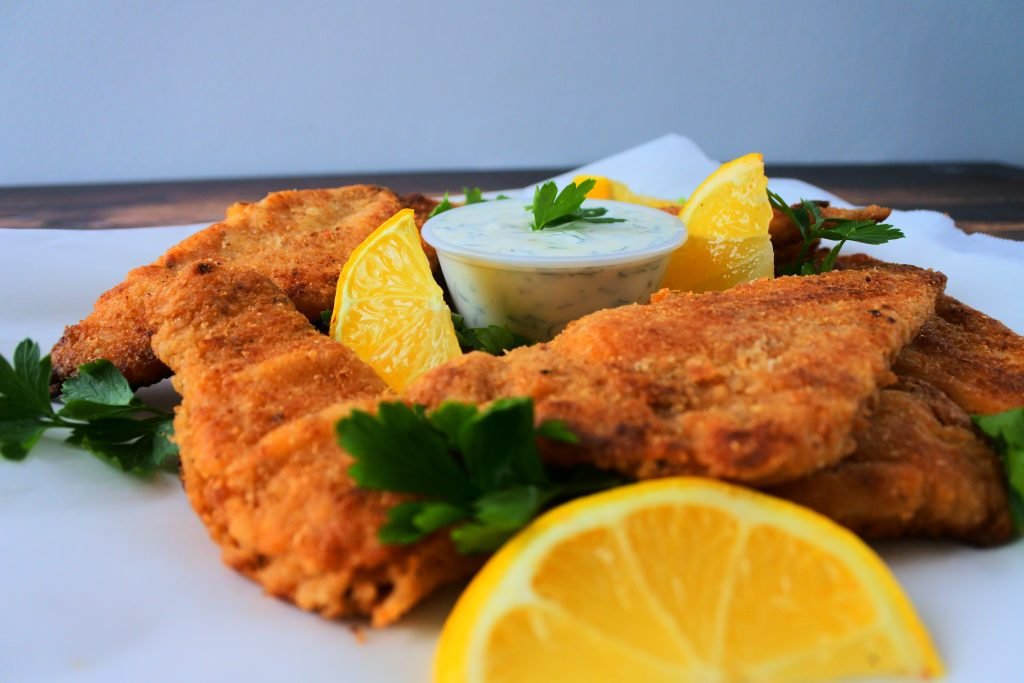 A head on image of lightly fried fish fillets served with a tartar sauce, lemon wedges and parsley