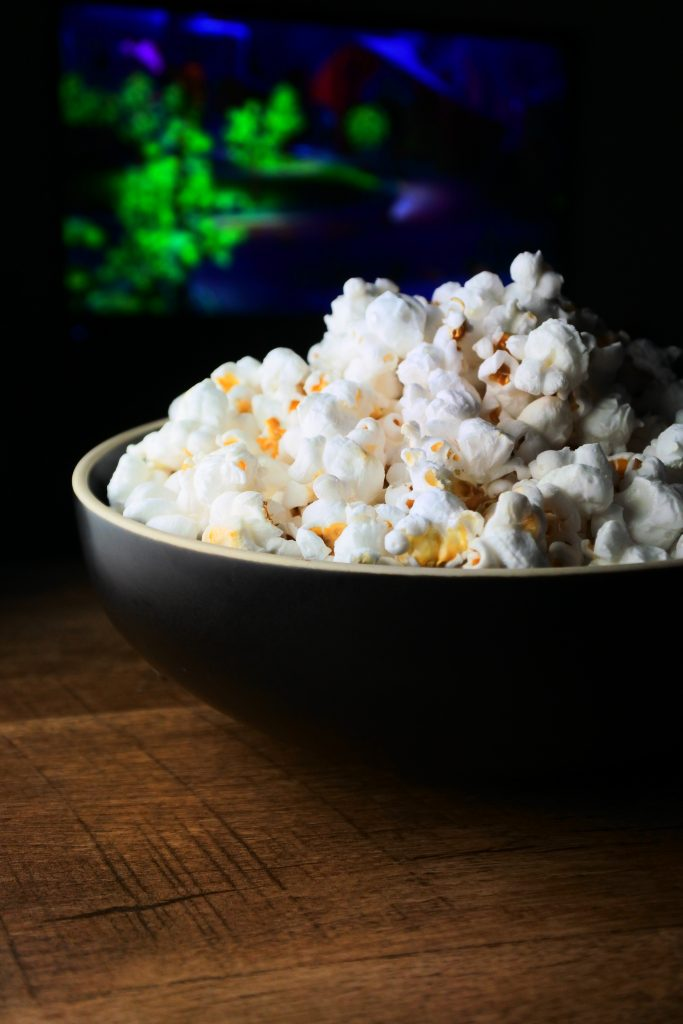 A close up head on image of of a bowl of popcorn with a movie playing in the background