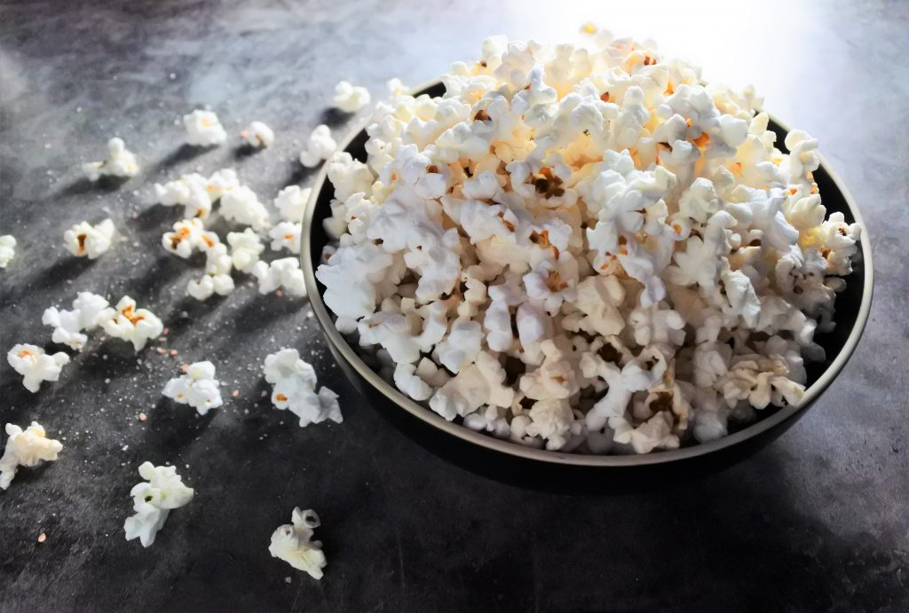 An angled overhead bowl of popcorn with scattered kernels and coarse grain salt on the work surface