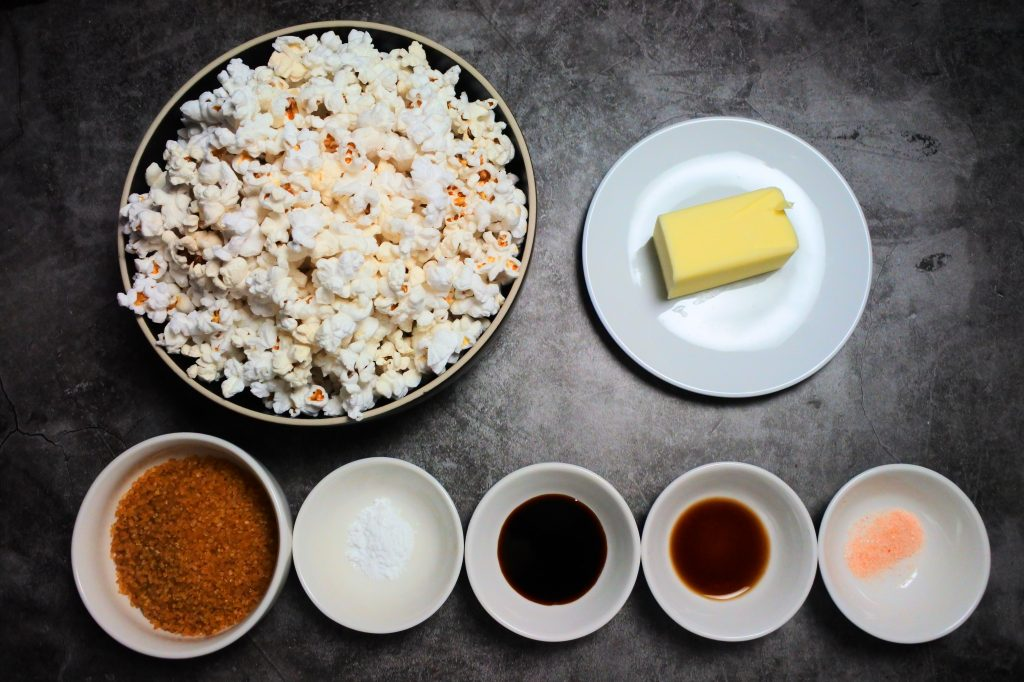An overhead image of ingredients for caramel popcorn including popped popcorn, butter, raw cane sugar, baking soda, molasses, vanilla extract and salt