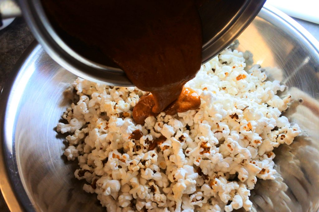 An angled overhead image of caramel being poured over popcorn in a bowl