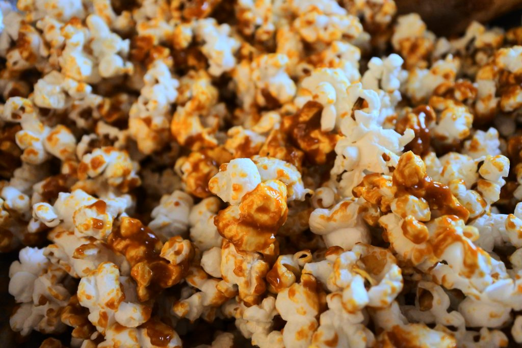 A close up image of caramel popcorn being mixed