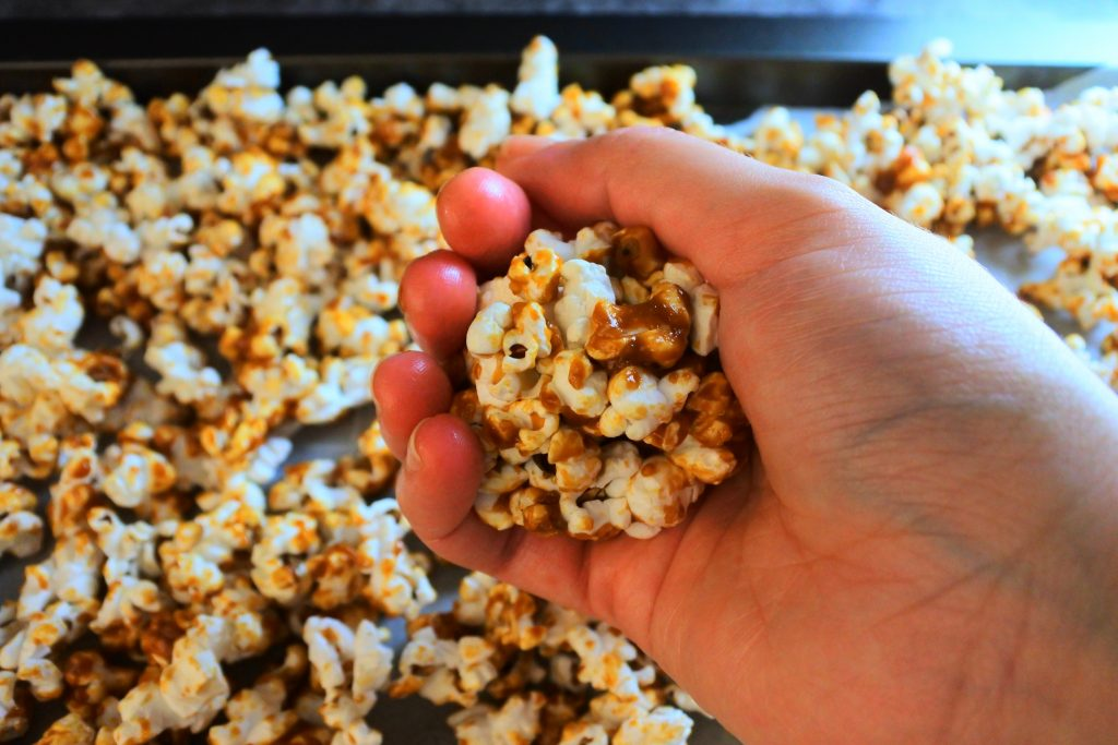An angled image of a hand molding a caramel popcorn ball
