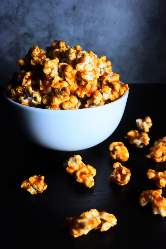 An angled image of a bowl of caramel popcorn with a few flakes spilled onto the counter
