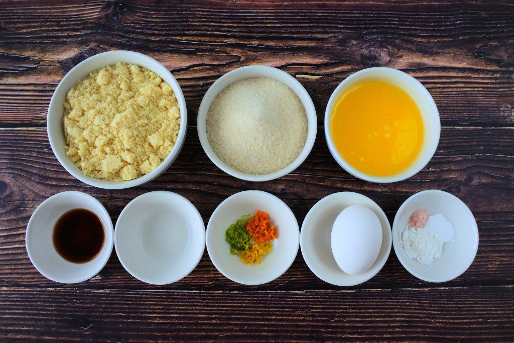 An overhead image of ingredients for a gluten free boterkoek / citrus butter cake including almond flour, sugar, butter, vanilla, orange extract, orange zest, egg, salt, baking powder and tapioca flour.