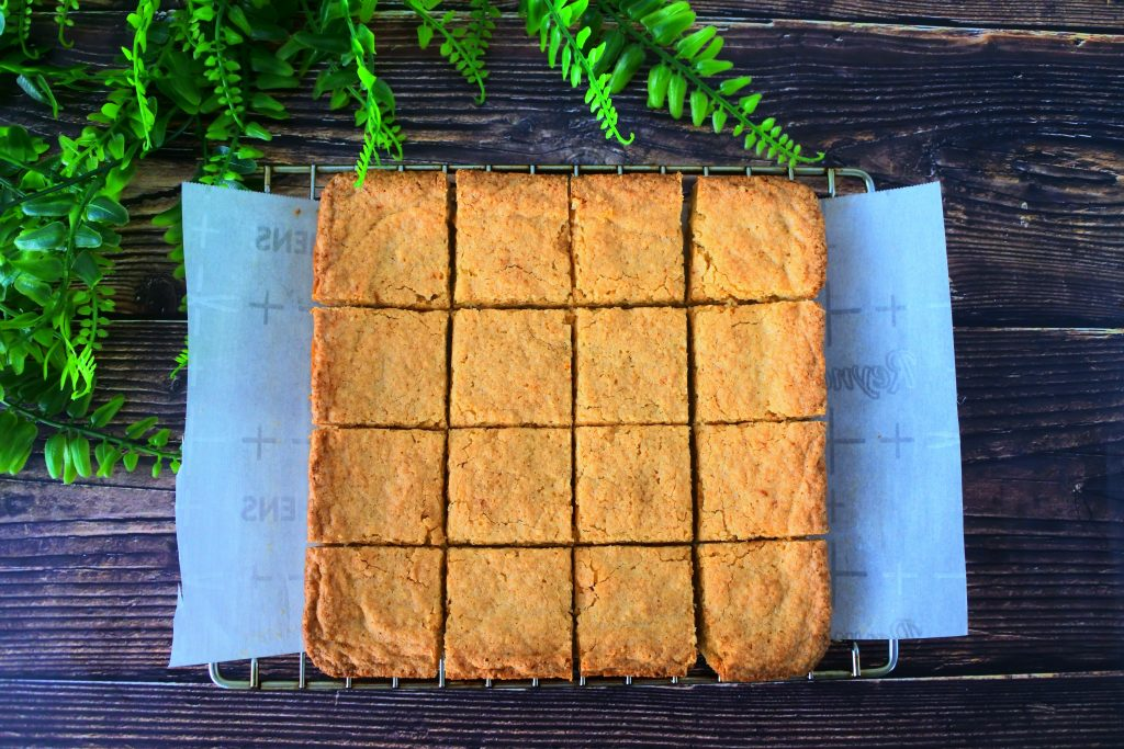 An overhead image of a tray of boterkoek on a cooling rack cut into squares