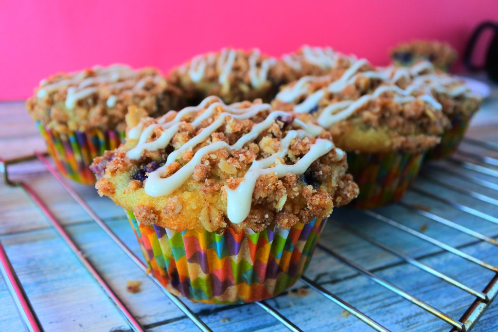 A head on image of a blueberry streusel muffin with a simple stripe of vanilla glaze on top