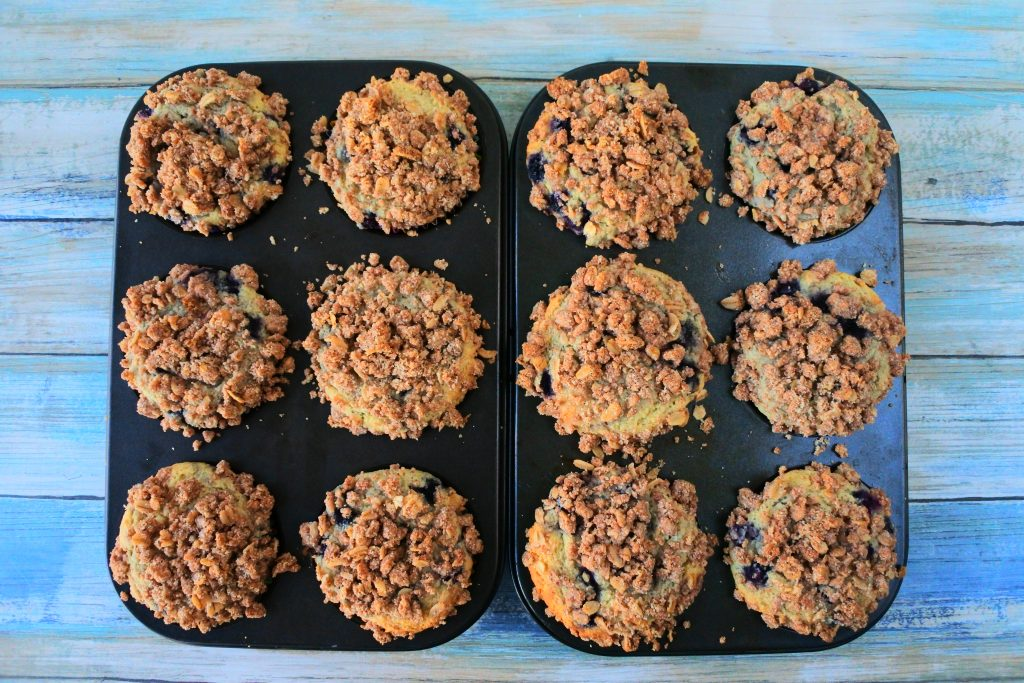 An overhead image of freshly baked blueberry streusel muffins in muffin molds